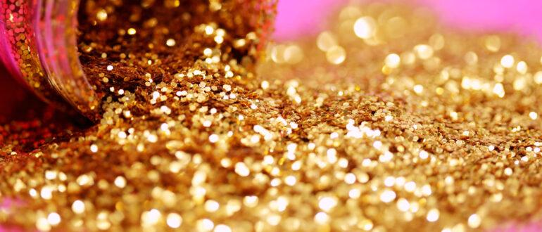 Gold, pinker Hintergrund, Goldstaub, Goldpartikel. Nuggets